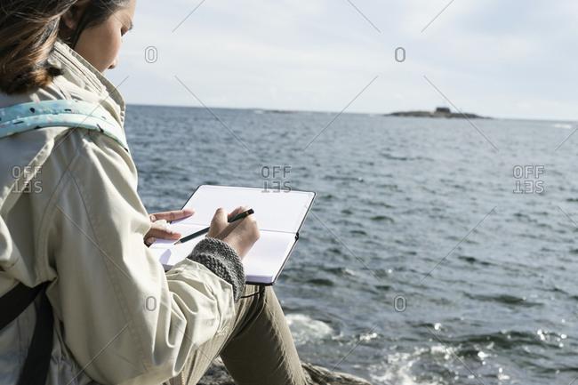 Teenage girl writing letter at seaside