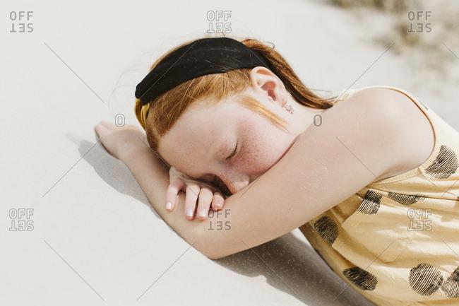 Girl sleeping on sand