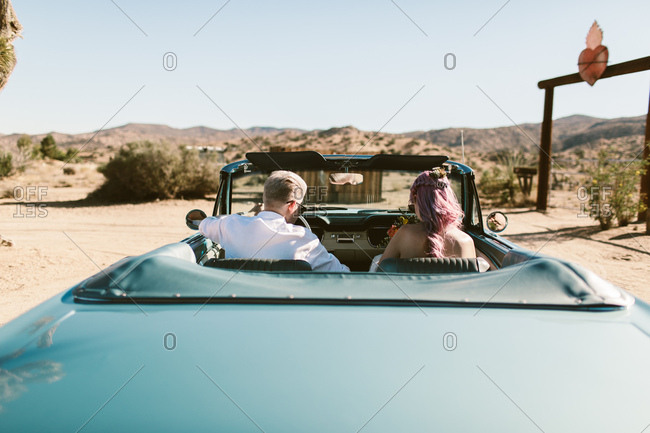 Bride and groom driving away in classic car in the desert