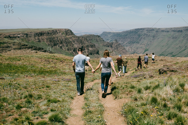 A family out on a nature walk holding hands at Kiger Gorge