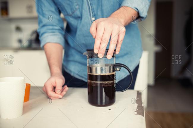 Man making French press coffee