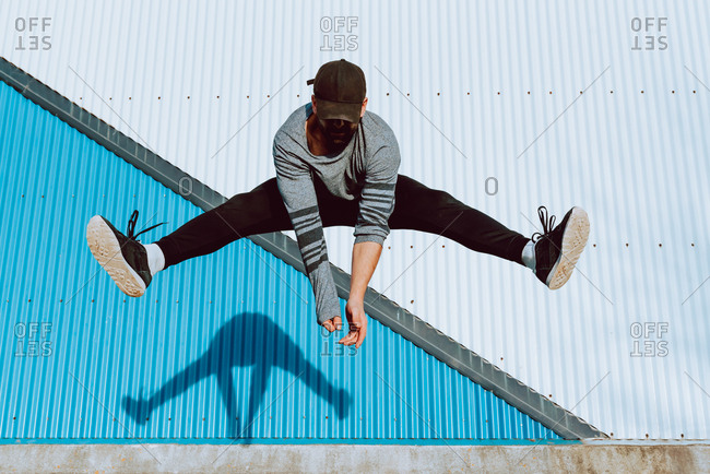 barefoot guy in stylish outfit performing flip near wall of modern building on city street