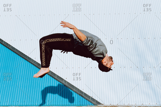 Side view of barefoot guy in stylish outfit performing flip near wall of modern building on city street