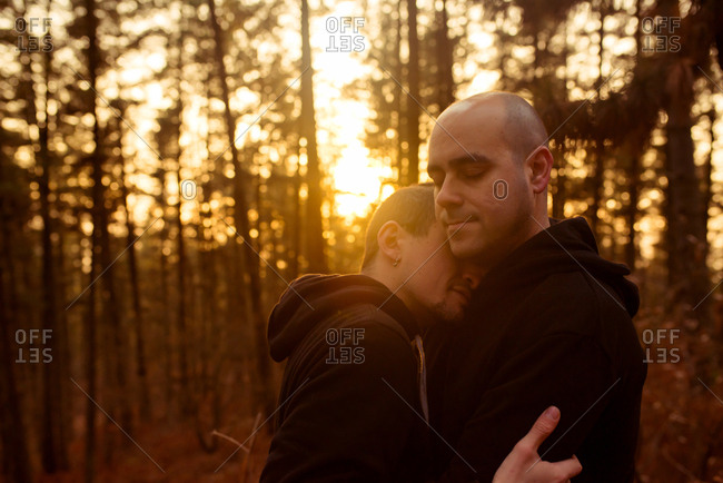Side view of homosexual couple with closed eyes embracing in forest in evening