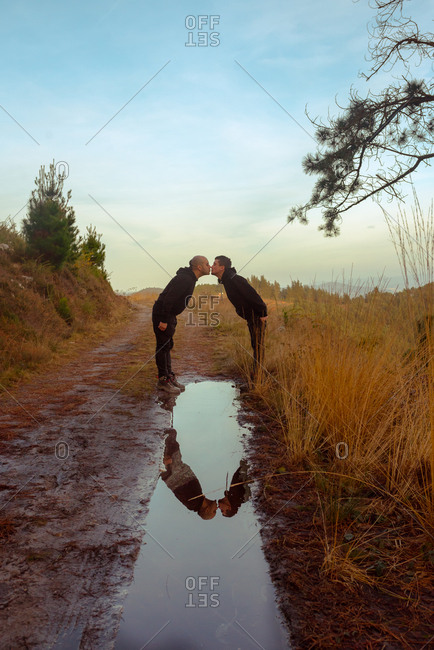 Water slop with reflection of homosexual couple embracing and kissing on road
