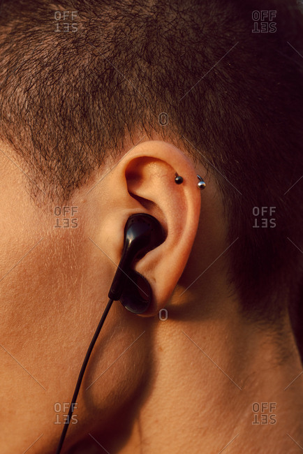 Side view of crop head of hipster with piercing and earphones in ear