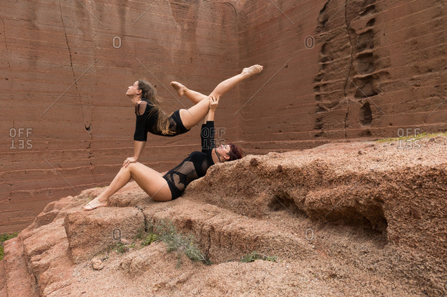 Side view of attractive young ladies in black underwear performing exercise on rough rocky surface in countryside