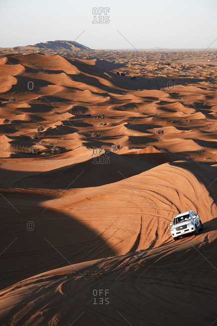 Safari on off-roader driving between sand dunes in sunny day in Dubai, United Arab Emirates