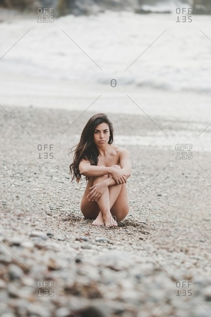 Attractive nude brunette lady looking at camera and sitting on coast near sea