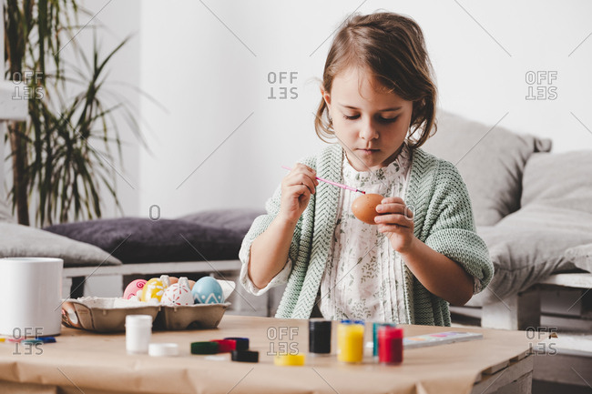 Girl with brush coloring chicken eggs at table in room