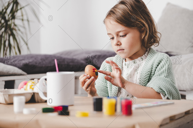 Girl coloring chicken egg at table
