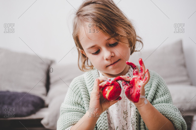 Girl with hands in colors painting chicken egg