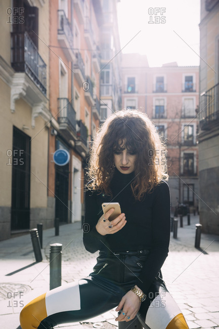 Young woman talking by phone in the street