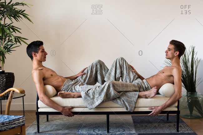 Stylish shirtless gay couple models posing and lying down in a padded modern bench