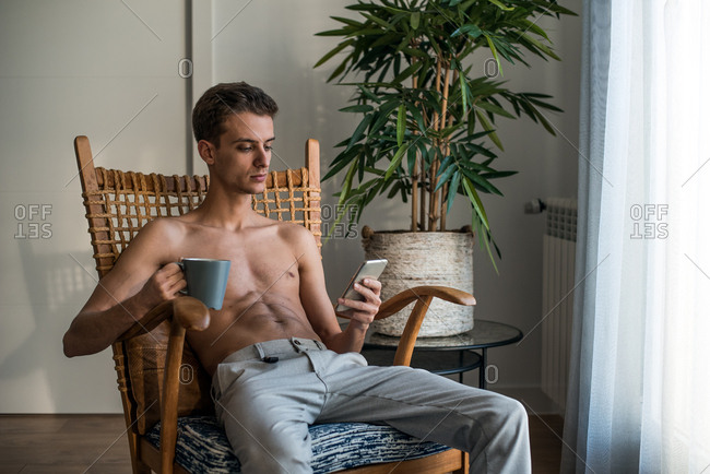 Stylish shirtless man sitting in a chair drinking coffee and on the mobile phone