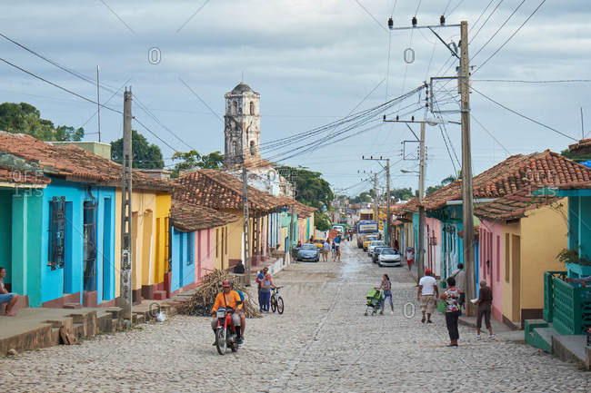 CUBA - DECEMBER 28, 2018: Old colourful houses on street near people and asphalt route with retro automobiles