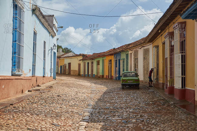 CUBA - DECEMBER 28, 2018: Old colourful houses on street near asphalt route with retro automobiles