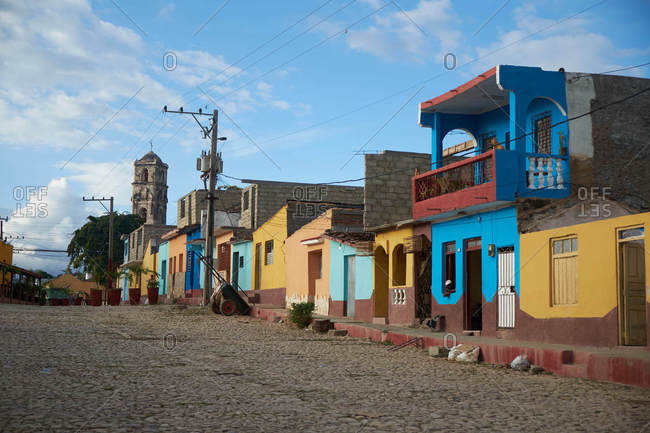 CUBA - DECEMBER 28, 2018: Old colourful houses on wide asphalt street and blue sky with clouds