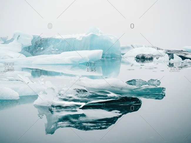 Picturesque view of ice on water surface between snow in winter in Iceland