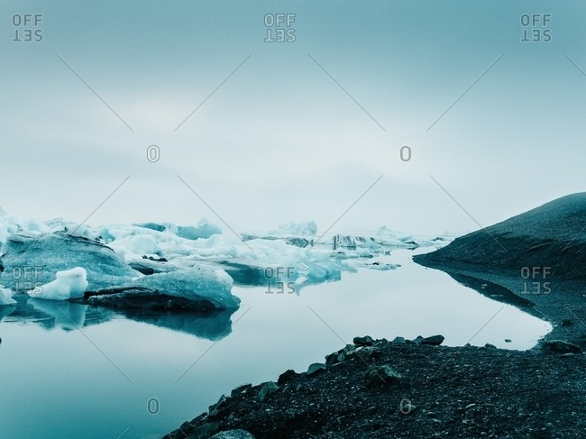 Picturesque view of ice on water surface between snow in winter in Iceland near a coastline