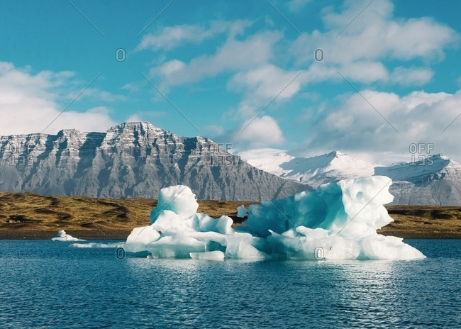 Picturesque view of ice on water surface in winter and blue heaven with clouds in Iceland near mountain and coastline
