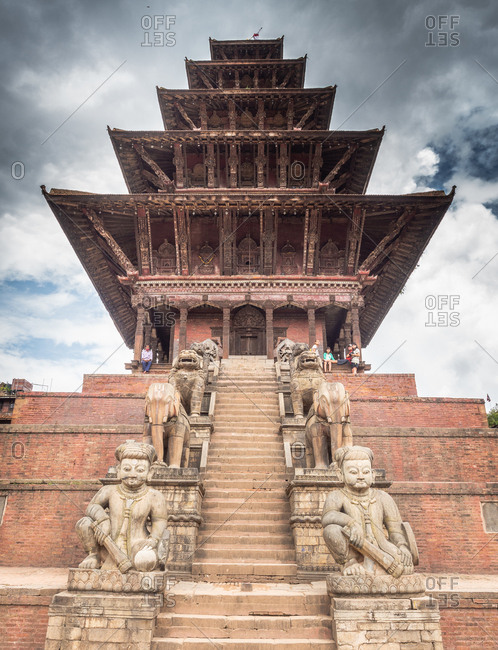 NEPAL, BHAKTAPUR - AUGUST 19, 2014: From below beautiful brick tower with steps and stone monuments and cloudy heaven