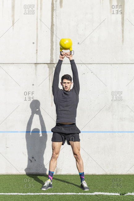 Young athletic male lifting heavy kettlebell on grass near grey wall in sunny day