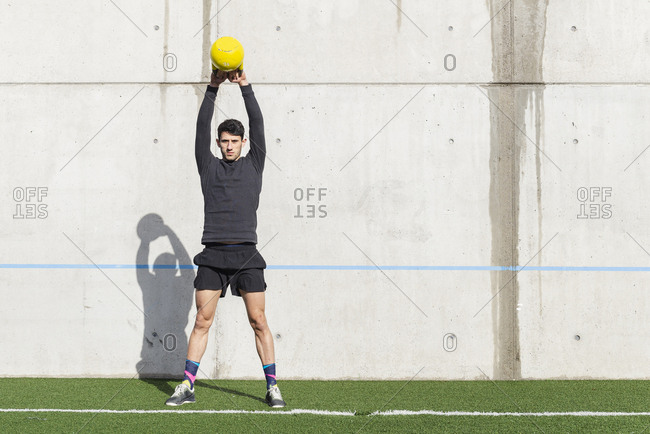 Side view of young athletic male tossing heavy training ball near tire and grey wall