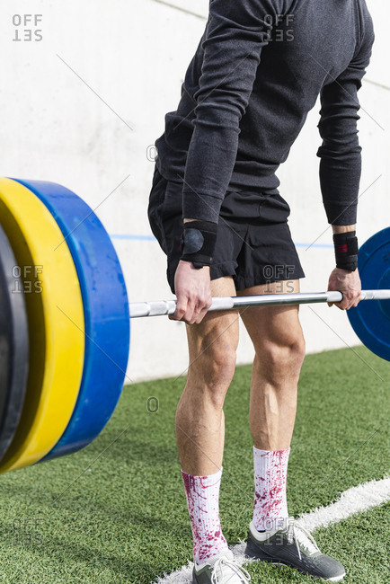 Crop young athletic male lifting heavy barbell with weights on grass