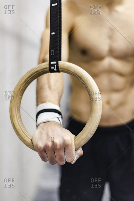 Crop shirtless male with press training with gymnastic rings in gym on blurred background