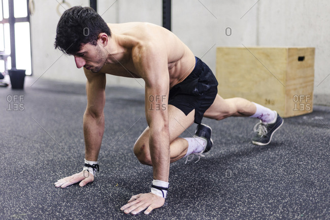 Young shirtless male doing plank and stretching legs near grey wall in gym