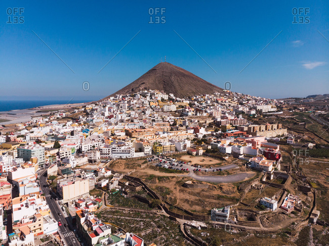 Drone view of small city of Galdar placed on Gran Canaria island with mountain peak under blue sky, Spain