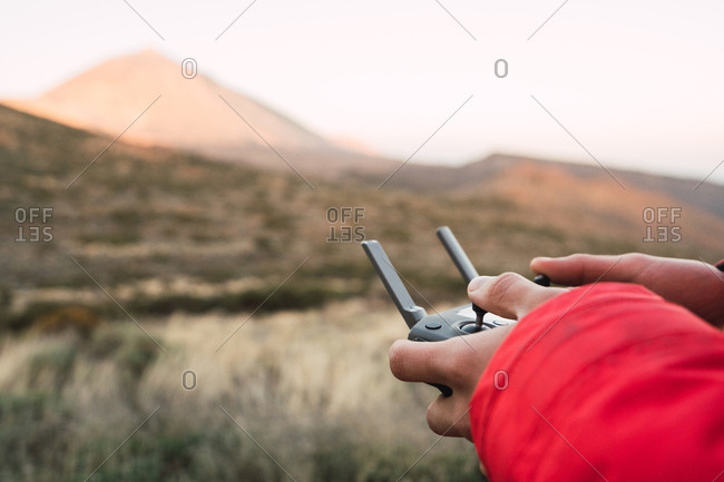 Side view of human holding joystick on land near top of mountain Teide in Tenerife, Canary Islands, Spain