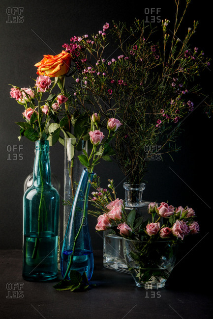 Vintage photo camera placed near glass vases with bouquets of lovely flowers on black background