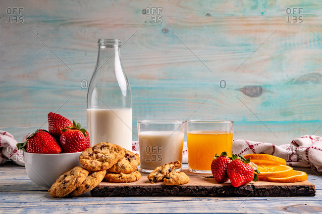 Glasses near fruits and cookies on table near napkin