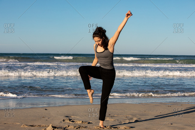 Young dancer on sand coast with waving sea and blue sky