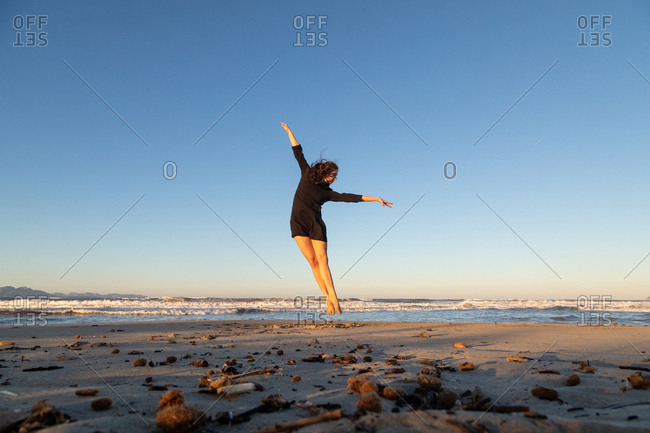 Young dancer posing on sand coast with waving sea and blue sky