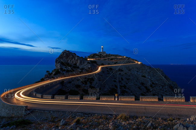 long exposure road at night with a light house in hill