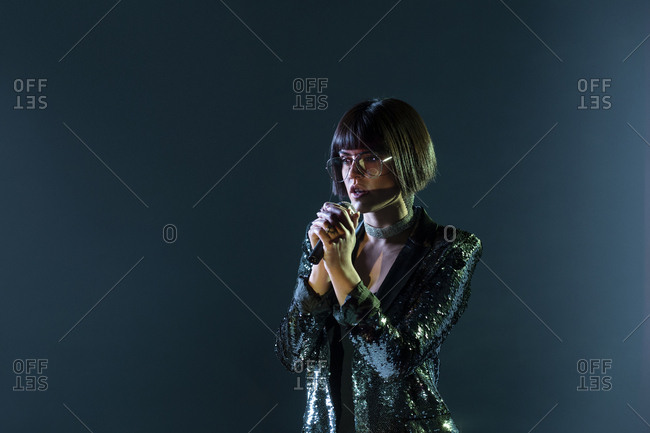 Stylish woman singing on stage