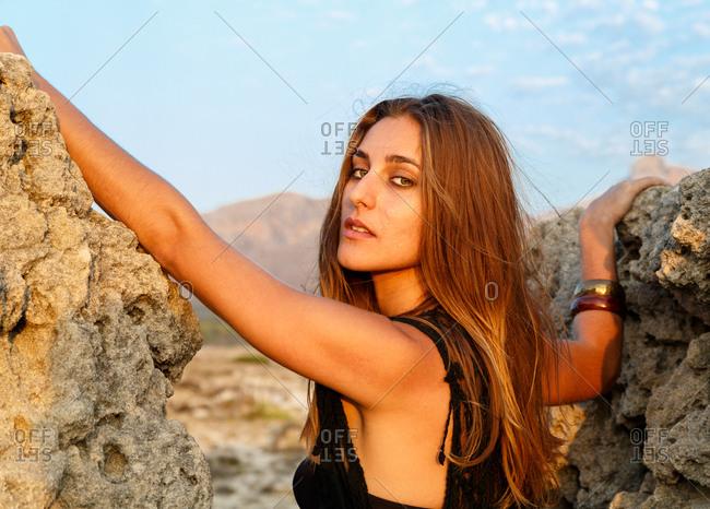 Slim woman in bikini posing between stones