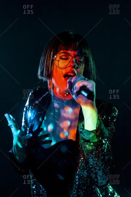 Stylish woman singing on stage