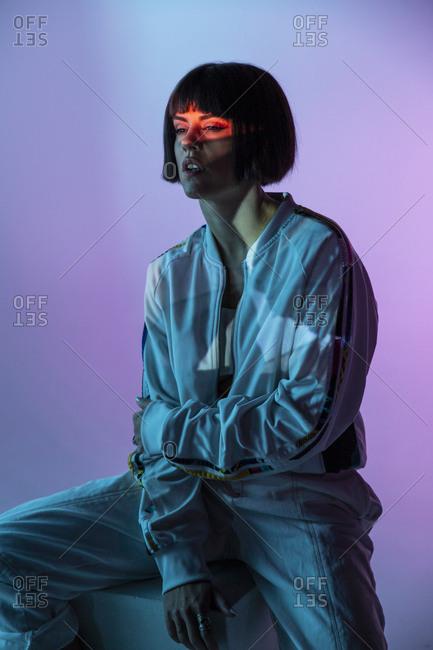 Trendy female sitting on cuboid