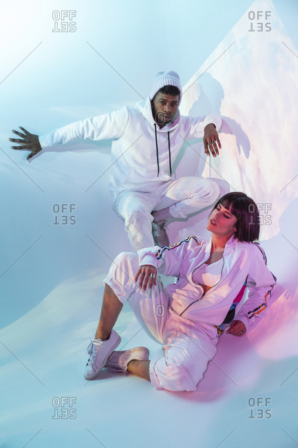 Young man and woman in stylish white sportswear posing for camera on blue background