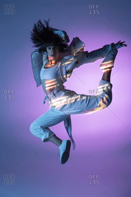 Energetic dancer jumping and looking at camera
