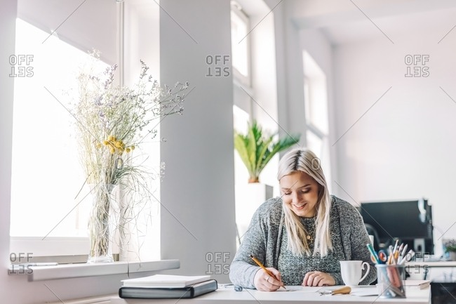 Smiling blond woman doing linearity and first sketches at table in light office near window