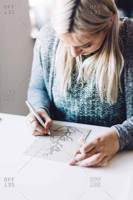 Young blond woman doing linearity and first sketches on paper at table in light office