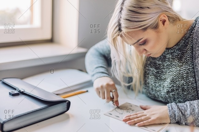 Busy blond woman doing linearity and first sketches at table in light office near window