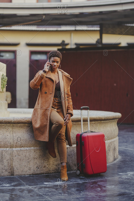 African American elegant woman with baggage talking on mobile phone and standing near monument on street