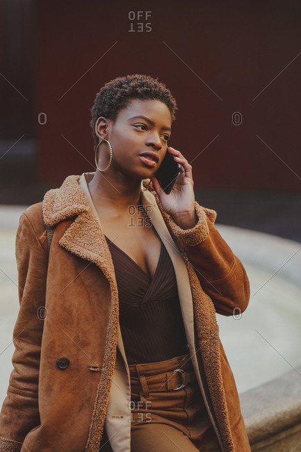 African American elegant woman talking on mobile phone and looking at camera on street