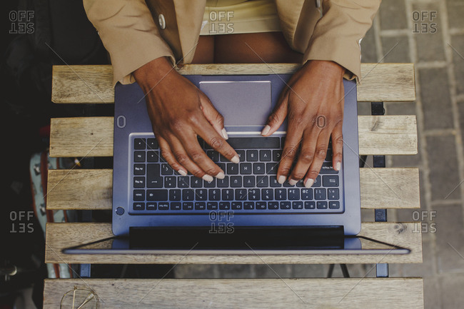 From above crop African American elegant woman sitting at table and typing on laptop in street cafe